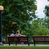 Deux personnes de dos assises sur un banc dans le parc Major à Ottawa en été.