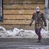 Un piéton masqué traverse une rue lors d'une journée de neige.