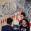Des femmes traversant une barrière de sécurité.