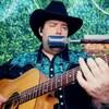 Un homme portant un chapeau de cowboy joue de la guitare.