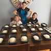 Trois jeunes filles devant un lot de pains prêts à passer au fourneau.