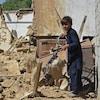 Un garçon tient un vélo endommagé dans les ruines d'une maison.