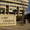 L'enseigne devant le palais de justice d'Edmonton avec l'édifice en arrière-plan.