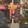 Deux pancartes sont superposées sur un poteau installé sur un terre-plein d'un boulevard où passent des voitures. Sur une des pancartes, on retrouve la photo d'un homme et sur l'autre, la photo d'une femme.