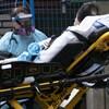 Une patiente est transportée par deux travailleurs de la santé, sur une civière.