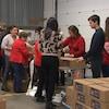 Une douzaine de personnes assemblent des paniers de Noël dans un entrepôt à Montréal.
