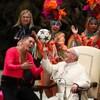 Le pape François, entouré d'artistes de cirque cubains, fait tourner un ballon de soccer sur son doigt et affiche un grand sourire.