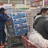 Un homme et son panier d'épicerie rempli de papier hygiénique dans un magasin.