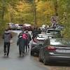 Des personnes marchent le long d'une file de voitures stationnées en bordure d'une route en forêt.