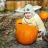Un enfant avec un déguisement du personnage de Yoda se tient près d'une citrouille.