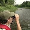Un homme qui regarde avec des jumelles sur un lac.
