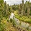 Deux personnes avancent en canot sur une rivière entourée d'une forêt dense.