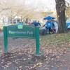 Un panneau inscrit Oppenheimer Park, avec des tentes en arrière-plan, dans un parc, et une rue à droite.