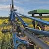 Trois caméras sont attachées à une barre en métal sur un tracteur vert qui roule dans un champ de canola aux fleurs jaunes.