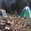 Un site de camping en Saskatchewan avec deux tentes et des bûches empilées.