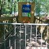 Une passerelle en bois qui est inaccessible aux passant puisqu'une affiche indique qu'elle est fermée au public.