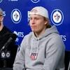 Deux joueurs de hockey sont assis devant des micros et parlent aux journalistes. L'un d'eux est Patrick Laine, qui est vêtu d'un chandail de coton ouaté et d'une casquette.