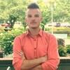 Un jeune homme arborant une chemise orange debout dans un espace vert