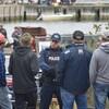 Un policier les bras croisés et six personnes de dos.