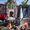 Des gens posent des fleurs devant un monument commémoratif.