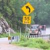 Un camion lourd circule sur une route. À l'avant-plan, on voit un panneau de vitesse indiquant 55 kilomètres à l'heure.