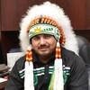 Ross Perley assis dans une salle et portant sa coiffe de chef autochtone.
