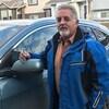 Pete Llewellyn, accoudé sur le rétroviseur d'une automobile dans un quartier résidentiel.