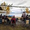 Des gens assis dehors autour d'un feu de camp.