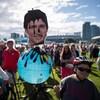 Un homme âgé tient un globe-terrestre avec le visage de Justin Trudeau couvert en partie de pétrole noir. Des manifestants sont en arrière-plan devant un centre-ville.