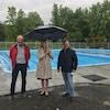 Deux hommes et une femme sourient devant une piscine.