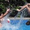 un homme en maillot de bain est dans une piscine avec une femme et un enfant, ils jouent avec une balle