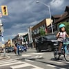 Photo d'une fillette qui roule sur la piste cyclable devant son frère et son père.