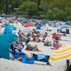 Des personnes sur une plage, dont certaines sont installées sous des tentes.