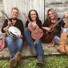 Trois femmes assises devant une grange avec leur instrument de musique à la main.