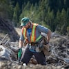 Un homme en habit de travail, avec des gants et une pelle à la main, entre de vieilles souches.