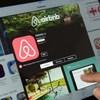 Un doigt touchant un écran sur lequel on voit la page d'accueil d'Airbnb.