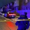 Un policier dans une rue la nuit devant un bandeau jaune de la police et une voiture de police.