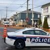 Une voiture de police est stationnée au centre d'une rue résidentielle, devant des banderoles de sécurité, bloquant le chemin.