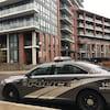 Photo d'une autopatrouille grise devant un immeuble en briques brunes.