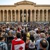 Des milliers de manifestants arborant des pancartes et des drapeaux sont de dos et font face au bâtiment du Parlement géorgien.