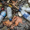 Des bouteilles de plastique vides traînant sur le sol mouillé.