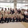 Le groupe de pompiers pose pour une photo à l'aéroport.