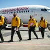 Les pompiers venus en renfort du Mexique marchent sur le tarmac de l'aéroport d'Abbotsford, à la sortie de l'avion.