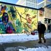 Un homme masqué passe devant une murale colorée illustrant une infirmière portant le masque accompagnée d'oiseaux et de feuilles d'arbres.