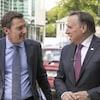 Le journaliste Patrice Roy et le premier ministre du Québec, discutent dans une rue de L'Assomption, en se regardant.