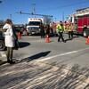 Une femme sur le trottoir observe un camion de pompier et une ambulance au milieu d'une rue.