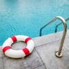 Une bouée de sauvetage déposée en bordure d'une piscine creusée.