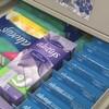 Des boîtes de serviettes hygiéniques et de tampons dans le tiroir d'un classeur.