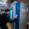 Devant une machine un peu plus grande qu'un guichet bancaire automatique, un homme pose sa main sur un scanneur situé à côté d'un écran d'information.