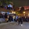 Des gens font la queue à l'extérieur d'un bar.